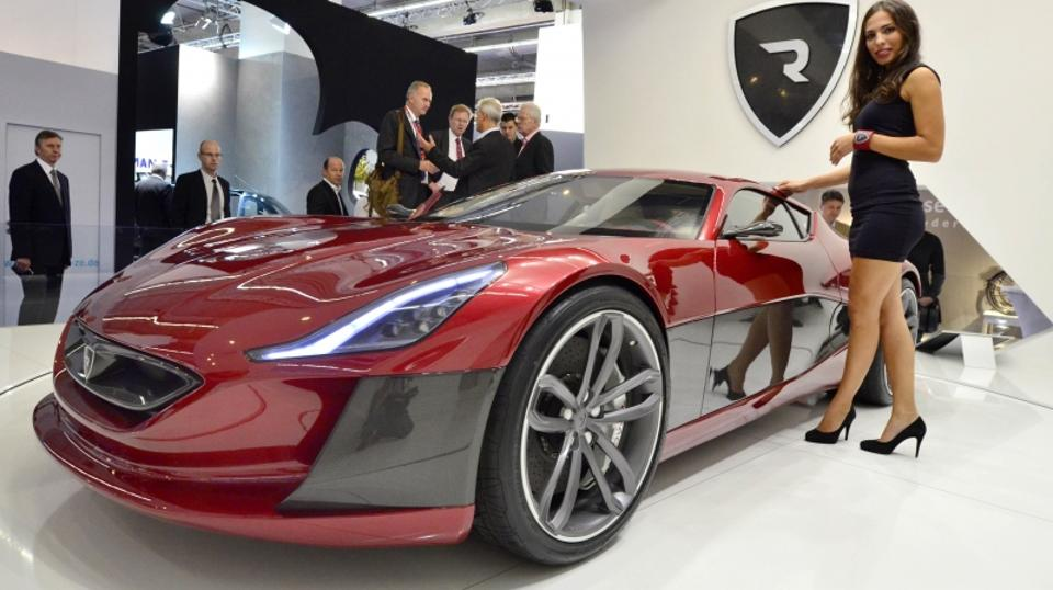 'A model poses next to an electric sportscar of Croatian car producer Rimac Automobili at the international motor show IAA (Internationale Automobil-Ausstellung) in Frankfurt/M, western Germany, on Se