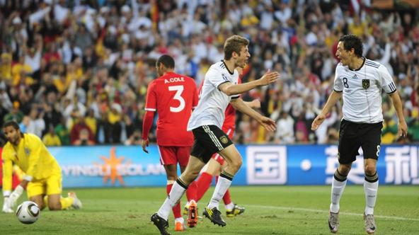 'Germany\'s midfielder Thomas Mueller (c) celebrates with team mate Germany\'s midfielder Mesut Ozil  after scoring a fourth goal during the 2010 World Cup round of 16 football match Germany vs. Engla