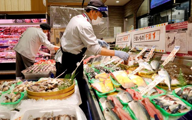 A staff wearing a face shield sells fish at Japan's supermarket group Aeon's shopping mall as the mall reopens amid the coronavirus disease (COVID-19) outbreak in Chiba