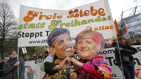 Protesters wearing masks depicting German Chancellor Angela Merkel and U.S. President Barack Obama as they demonstrate against Transatlantic Trade and Investment Partnership (TTIP) agreement ahead of Obama's visit in Hanover, Germany April 23, 2016.  REUT