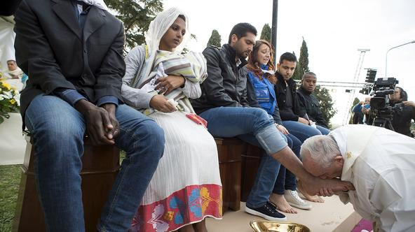 Pope Francis kisses the foot of a refugee during the foot-washing ritual at the Castelnuovo di Porto refugees center near Rome, Italy, March 24, 2016. Pope Francis on Thursday washed and kissed the feet of refugees, including three Muslim men, and condemn