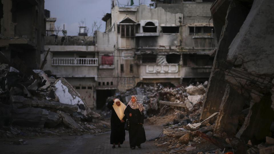 Palestinian women walk near the ruins of houses, which witnesses said were destroyed by Israeli shelling during the most recent conflict between Israel and Hamas, in the east of Gaza City December 1, 2014. According to housing minister Mufeed al-Hasayna,