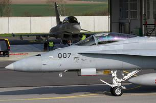 FILE PHOTO: A Swiss Air Force F/A-18C Hornet passes in front of a Eurofighter Typhoon jet during tests in Payerne