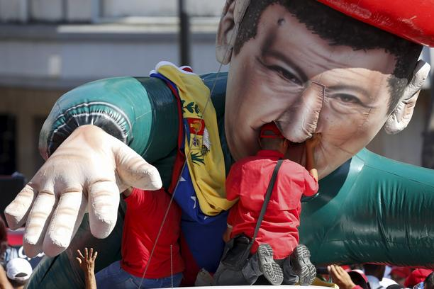 A worker of the Venezuelan state oil company PDVSA tries to attach the national flag to a giant inflatable figure of Venezuela's late President Hugo Chavez, during a meeting with Venezuela's President Nicolas Maduro outside Miraflores Palace in Caracas Ja