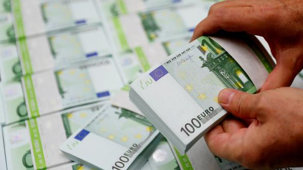 FILE PHOTO: An employee checks 100 Euro banknotes at the Money Service Austria company's headquarters in Vienna