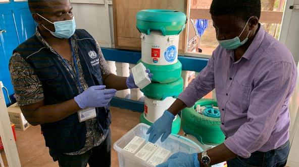 Workers from the World Health Organization inspect Ebola vaccines stored in an Arktek ultra-cold vaccine storage cylinder seen in the background in Mbandaka