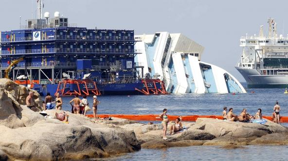 'People sunbathe in front of the capsized cruise liner Costa Concordia lying surrounded by cranes outside Giglio harbour July 17, 2013. The trial of the captain of the Costa Concordia cruise ship, whi