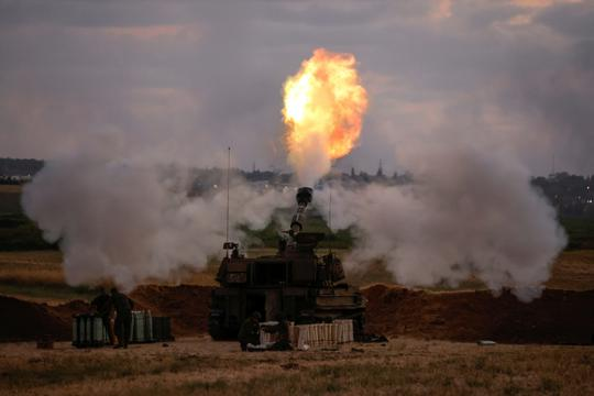 Israeli soldiers work at an artillery unit as it fires near the border between Israel and the Gaza strip, on the Israeli side