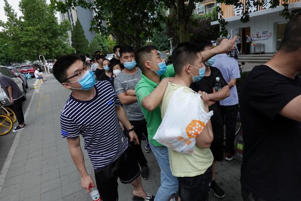 People wearing face masks wait in a line to receive nucleic acid tests in Beijing