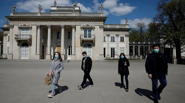 FILE PHOTO: People wearing protective masks enjoy walking in the Lazienki Royal Park after loosening of the lockdown measures by the government due to the coronavirus disease (COVID-19) in Warsaw