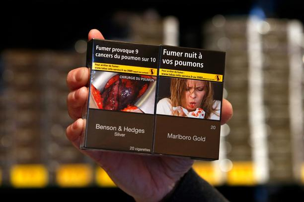 A tobacconist dispalys new cigarette packs, plain with unbranded packaging and the health warnings,