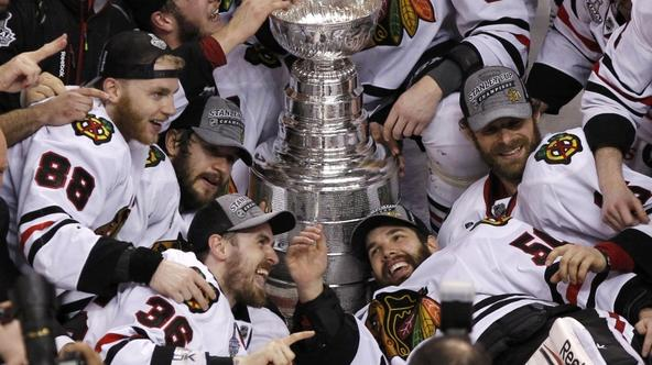 'Chicago Blackhawks\' Patrick Kane (L), Dave Bolland (C) and goalie Corey Crawford (R) celebrate with the Stanley Cup after they defeated the Boston Bruins in Game 6 of their NHL Stanley Cup Finals ho