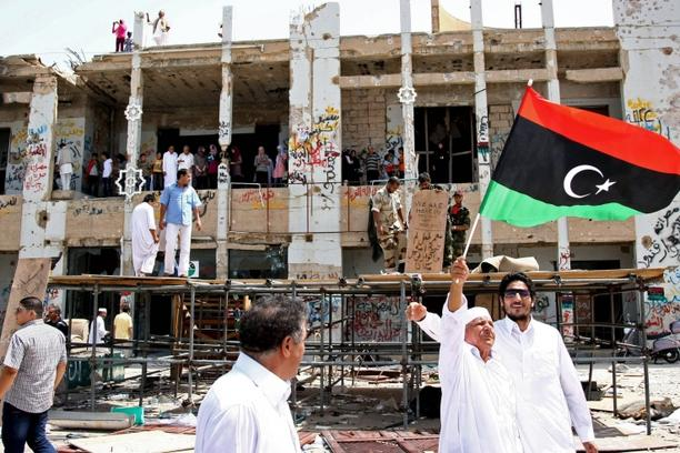 \'A Libyan elderly man waves the rebellion\'s flag as residents of Tripoli tour the destroyed Bab al-Aziziyah former headquarters of Libyan leader Moamer Kadhafi on September 1, 2011, as rebel forces