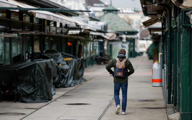 FILE PHOTO: A person passes closed restaurants and shops at a market after the local government extended the lockdown due to the coronavirus disease (COVID-19) outbreak in Vienna,
