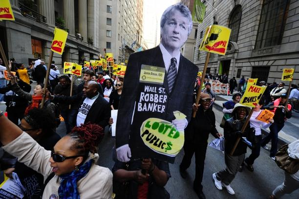 'Labor-Community Coalition activists march down Wall Street holding a cutout of JP Morgan CEO Jamie Dimon, during a protest against budget cuts and bank practices, in New York, May 12, 2011.Thousands
