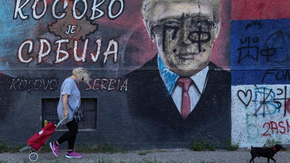 Woman walks with a dog in front of a mural depicting U.S. President Trump in Belgrade
