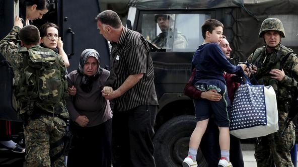 People are evacuated with an armored vehicle near a police checkpoint in Kumanovo, Macedonia, May 9, 2015. Explosions and heavy gunfire rocked the town in northern on Saturday as police moved against what authorities described as an