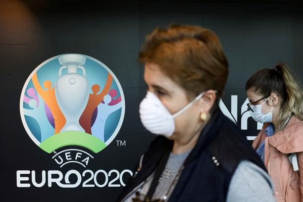 FILE PHOTO: Travellers pass by a logo of the 2020 UEFA European Football Championship displayed on a wall inside Bucharest Henri Coanda International Airport