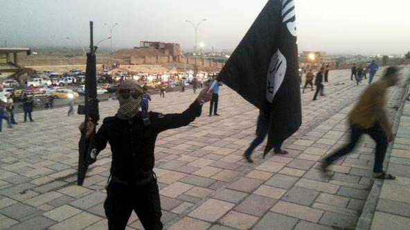 A fighter of the Islamic State of Iraq and the Levant (ISIL) holds an ISIL flag and a weapon on a street in the city of Mosul, Iraq, in this June 23, 2014 file photo. To match Special Report MIDEAST-CRISIS/IRAQ-ISLAMICSTATE      REUTERS/Stringer/Files