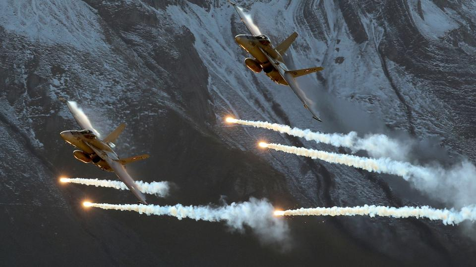 FILE PHOTO: Swiss Air Force F/A18 Hornet fighter jets release flares over the Axalp
