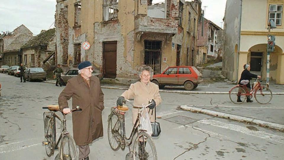 'A Croatian Serb couple pushes their bicycles 18 November downtown Vukovar in Croatia's disputed eastern Slavonia region. Croatians in eastern Slavonia today commemorated the 4th anniversary of the f