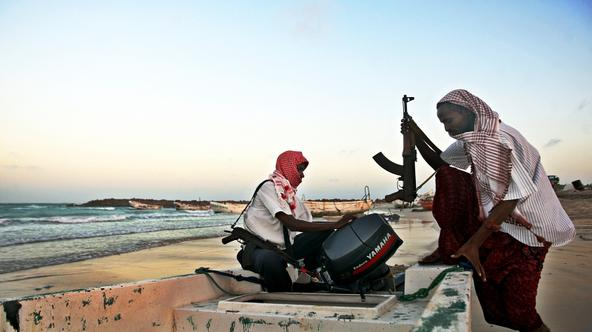 \'Photo taken on January 4, 2010 shows armed Somali pirates carrying out preparations to a skiff in Hobyo, northeastern Somalia, ahead of new attacks on ships sailing in the Gulf of Aden. Greek cargo