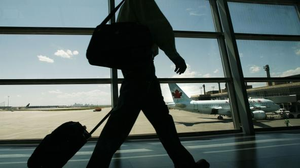 'An Air Canada passenger walks to catch his plane at the Calgary International Airport in Calgary, Alberta, June 17, 2008. Air Canada will cut 2,000 jobs and shrink its capacity by 7 percent as runawa