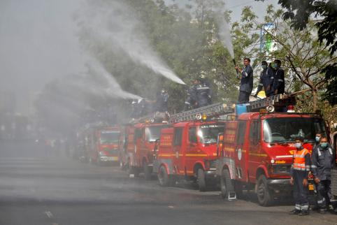 Members of Fire and Emergency Services decontaminate a road in Ahmedabad