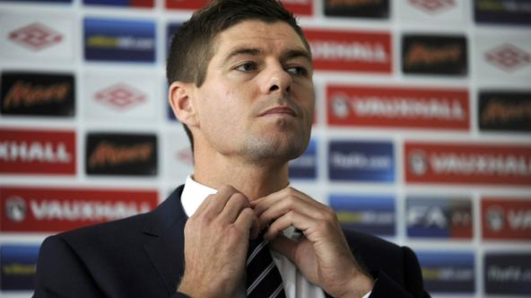 'England\'s national team player Steven Gerrard adjusts his tie as he attends a press conference during the EURO 2012 soccer tournament in Krakow June 25, 2012.  REUTERS/Pawel Ulatowski (POLAND  - Tag