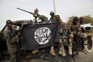 Nigerien soldiers hold up a Boko Haram flag that they had seized in the recently retaken town of Damasak, Nigeria, March 18, 2015. Chadian and Nigerien soldiers took the town from Boko Haram militants earlier this week. The Nigerian army said on Tuesday i