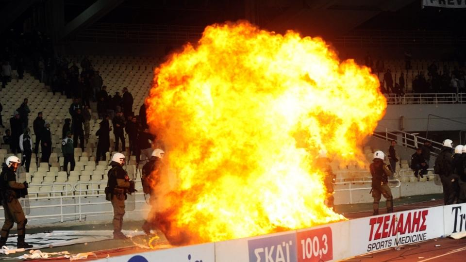 'Greek riot police watch a fire set by a petrol bomb as they clash with Panathinaikos supporters during a Greek Super League football game against Olympiakos in Athens on March 18, 2012.   AFP PHOTO/