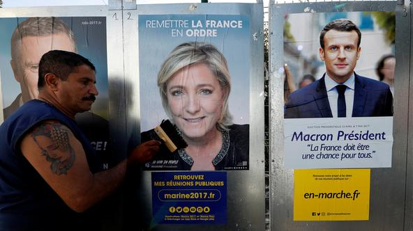 Sauveur, a member of the French National Front (FN) political party pastes a poster on a official billboard for French National Front (FN) political party leader Marine Le Pen as part of the 2017 French presidential election campaign in Antibes Sauveur, a