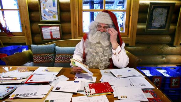 'A man dressed as Santa Claus looks over some of the thousands of letters received at the Santa Claus Office located on the Arctic Circle near Rovaniemi November 26, 2009. REUTERS/Bob Strong  (FINLAND