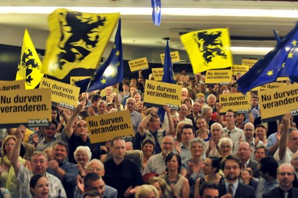 'people waving flemish flags as the chairman of the Flemish nationalist party N-VA, Bart De Wever (4G) surrounded with candidates sing the national Flemish anthem at the end of his seepch on June 6, 2