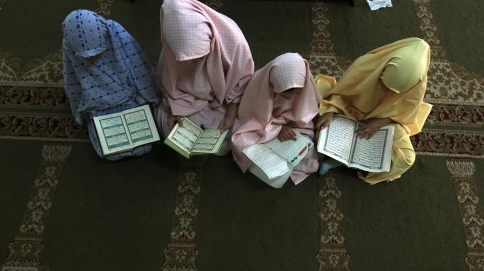 'Palestinian girls attend a class on how to read the Koran, Islam's holy book, at a camp in a local mosque in Gaza City on June 11, 2012. AFP PHOTO/MAHMUD HAMS'