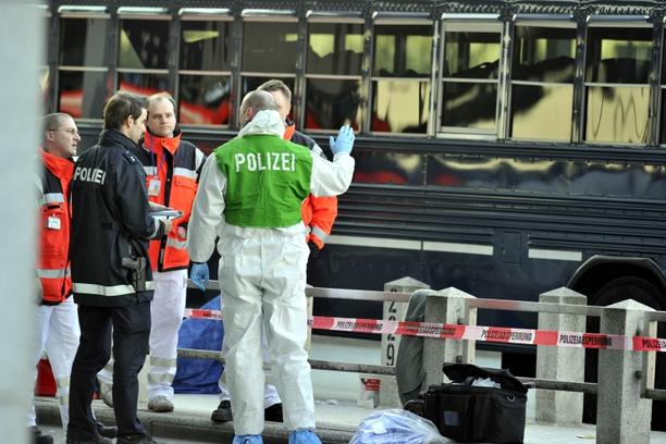 'Policemen and ambulance men stand in front of a US military bus after a shooting on March 2, 2011 at the airport in Frankfurt/M., western Germany. Two people were killed and two seriously injured in