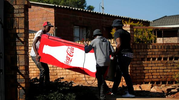 Locals carry a Cocacola branded refrigerator they looted at a nearby shop during protests in Atteridgeville, a township located to the west of Pretoria Locals carry a Cocacola branded refrigerator they looted at a nearby shop during protests in Atteridgev