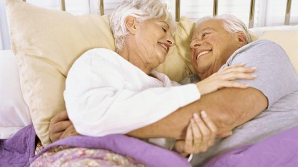 \'High angle view of a senior couple lying on the bed, hugging\'