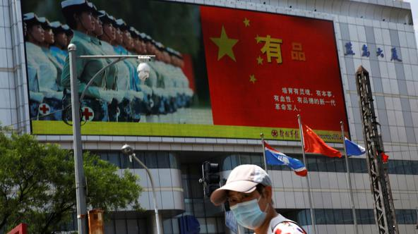 Pedestrian wearing a face mask walks past a screen showing an image of Chinese People's Liberation Army (PLA) soldiers next to a Chinese national flag, on the day of the opening session of the National People's Congress (NPC), in Beijing