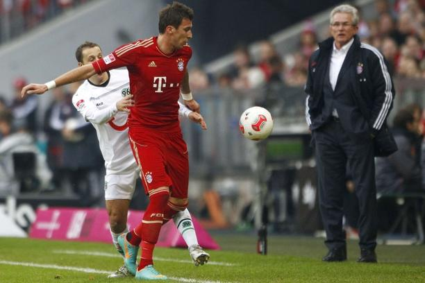 'Bayern Munich\'s Mario Mandzukic (C) is challenged by Steven Cherundolo (L) of Hanover 96 next to Bayern Munich coach Jupp Heynckes (R) during their German first division Bundesliga soccer match in M