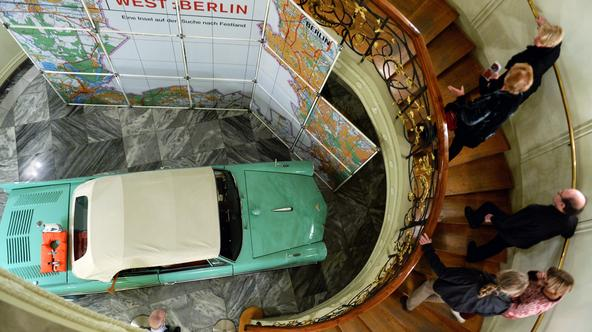 Visitors look at the buoyant convertible 'Amphicar' from the 1960s on the opening day of the exhibition 'WEST:BERLIN - An island in search of mainland' at the Stadtmuseum Berlin in Berlin, Germany, 13 November 2014. The show which features about 500 exhib