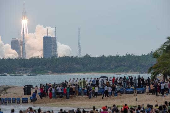 FILE PHOTO: People watch from a beach as the Long March-5B Y2 rocket, carrying the core module of China's space station Tianhe, takes off from Wenchang