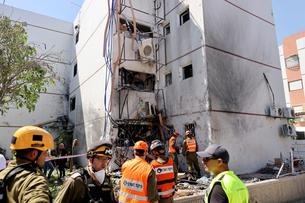 Israeli soldiers work at a damaged building following a rocket attack from Gaza, in Ashdod