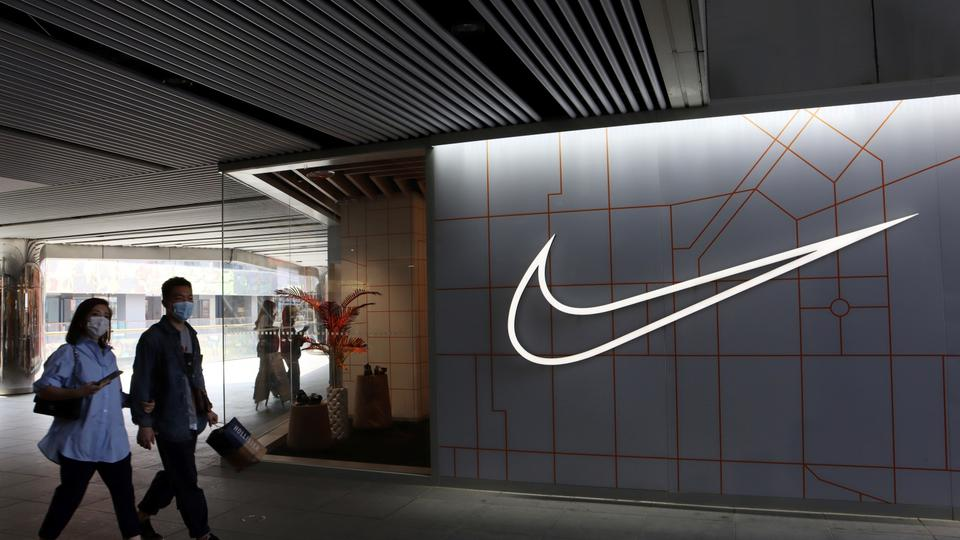 People walk past a Nike Inc store at a shopping complex in Beijing