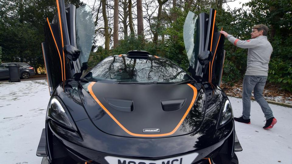Glynn displays his most recently acquired McLaren at his home in Headley Down