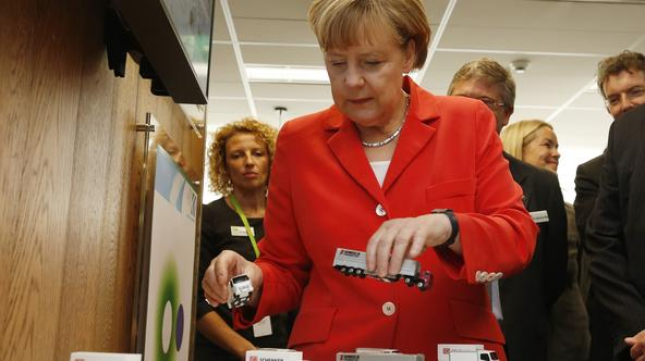 Germany's Chancellor Angela Merkel plays with models of trucks during an interactive demonstration of transportation logistics during her visit to the Future Logistics Living Lab in Sydney, November 17, 2014. Merkel is in Sydney following the G20 leaders