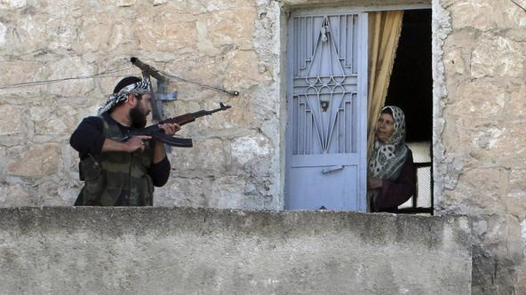 'A member of the Free Syrian Army talks to a woman during a patrol to search for pro-government forces in Harem town, Idlib Governorate, in this October 26, 2012 file photo. As Syria's rebellion has