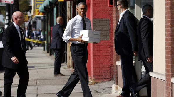U.S. President Barack Obama carries boxes of pastries into a Pat Quinn campaign office in Chicago, Illinois October 20, 2014. Quinn is running for re-election as Governor of Illinois.  REUTERS/Kevin Lamarque (UNITED STATES - Tags: POLITICS ELECTIONS)