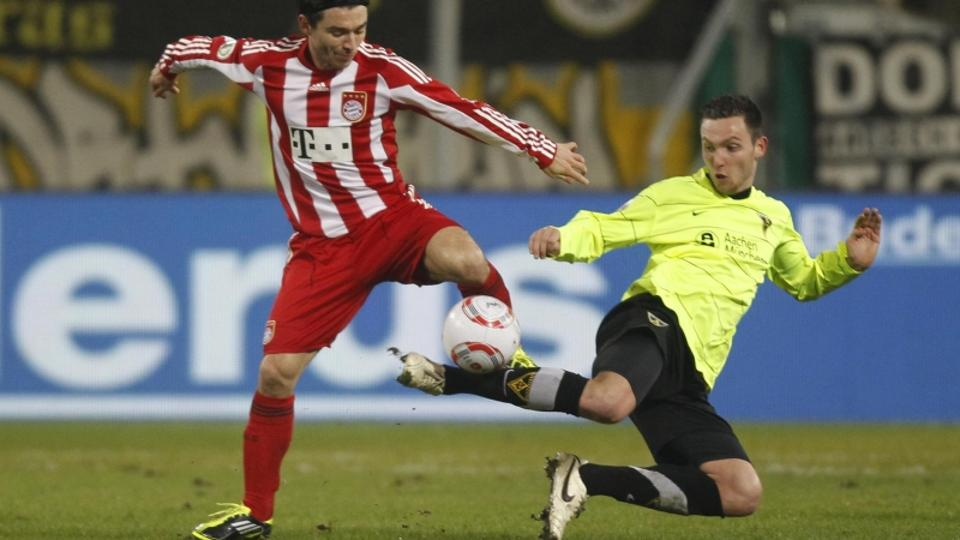 \'Bayern Munich\'s Danijel Pranjic (L) challenges Alemannia Aachen\'s Marco Hoeger during their German soccer cup (DFB-Pokal) quarter-final match in Aachen, January 26, 2011. REUTERS/Alex Domanski (GE