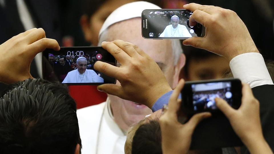Pope Francis is pictured by mobile phones as he arrives to lead a special audience for Vatican employees and their families at the Paul VI's hall at the Vatican December 22, 2014.  REUTERS/Alessandro Bianchi (VATICAN - Tags: RELIGION TPX IMAGES OF THE DAY
